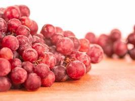 uvas vermelhas em uma tábua