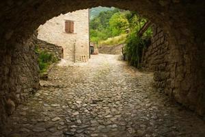 arcada medieval e rua de paralelepípedos foto