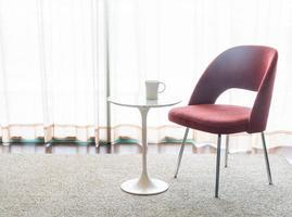 cadeira vermelha e mesa com uma xícara de café foto
