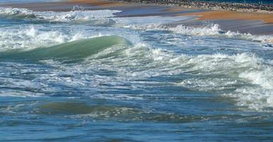 ondas quebrando na praia foto