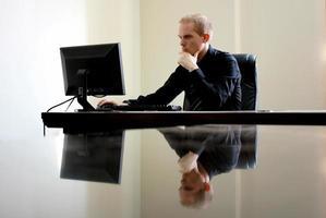 homem branco caucasiano sentado em frente a um computador atrás de uma mesa de vidro foto