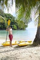 homem na praia com remo de caiaque foto