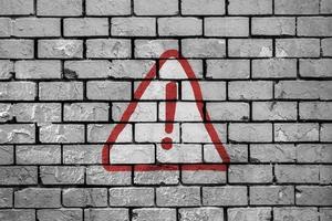 sinal de alerta pintado em parede de tijolos foto