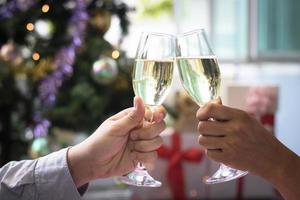 duas pessoas tilintando taças de champanhe em comemoração foto