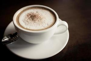 close-up de um café com leite em uma mesa de madeira foto