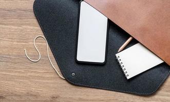 maquete de smartphone com bloco de notas e lápis em uma bolsa de couro