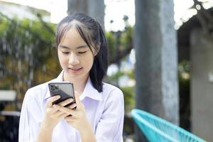 garota tailandesa usando um telefone celular