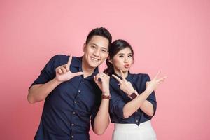 casal asiático feliz fazendo gesto de amor com a mão foto