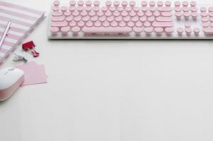 teclado de computador rosa com mouse e suprimentos em uma mesa branca