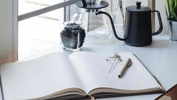 caderno aberto ao lado de uma cafeteira