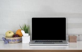 maquete de laptop ao lado de frutas em uma mesa