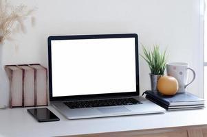 maquete de laptop em uma mesa com uma laranja e itens de escritório foto