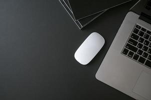 laptop, mouse e livros em uma mesa preta