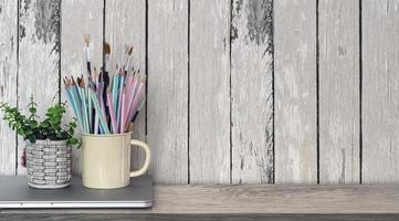 xícara de lápis e planta de casa no laptop na mesa de madeira
