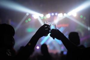 silhuetas de pessoas tilintando copos em uma boate
