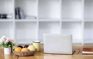 laptop com frutas e café em uma mesa foto