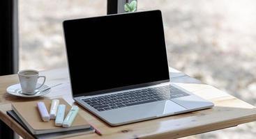 maquete de laptop em uma mesa perto de uma janela foto