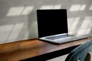 maquete de laptop em uma mesa de madeira foto