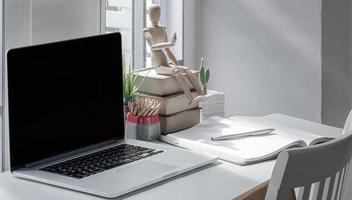 espaço de trabalho com um laptop e suprimentos em uma mesa