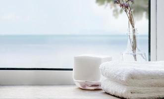 pilha de toalhas de banho limpas em uma mesa de madeira perto de uma janela