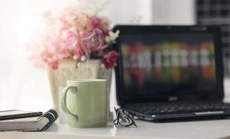 vapor saindo de uma caneca verde em um escritório doméstico foto