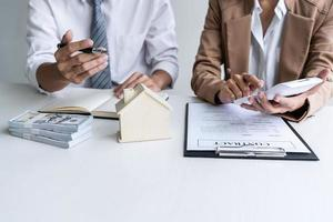 duas pessoas revisando o contrato imobiliário foto