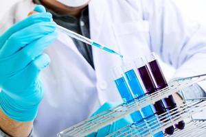 close-up de profissionais colocando líquido em tubos de ensaio foto