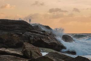 pescador nas rochas durante o pôr do sol foto