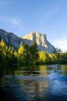 rio com árvores e montanhas ao fundo foto