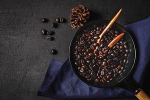 café cru torrado em uma panela foto