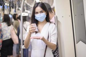 mulher usando desinfetante para as mãos