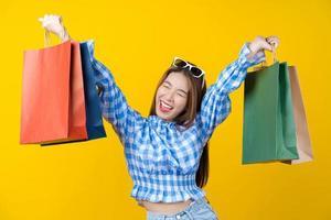 jovem atraente carregando sacolas coloridas foto