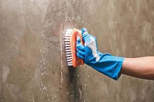 close-up de uma pessoa limpando uma parede com uma escova