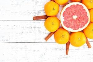 tangerinas doces maduras e especiarias, em fundo de madeira foto