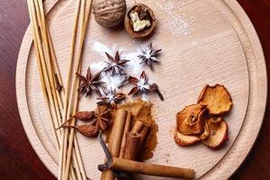 paus de canela, frutas secas em uma placa de madeira foto