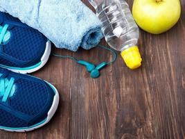 tênis, água, toalha e fones de ouvido no fundo de madeira foto