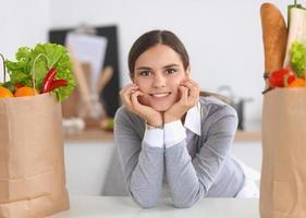 jovem mulher segurando a sacola de compras com legumes em pé foto