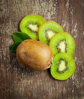 kiwi inteiro fresco e sua metade fatiada foto