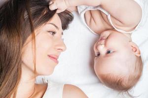 mãe feliz com um bebê deitado em uma cama branca foto