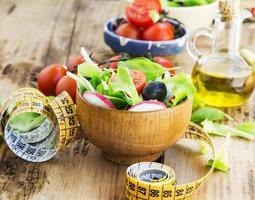 salada de legumes saudáveis com fita métrica. conceito de dieta foto