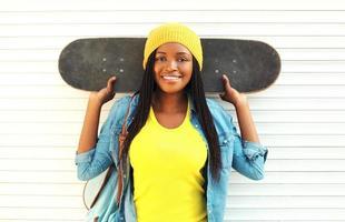 moda muito jovem mulher africana sorridente com skate em co foto