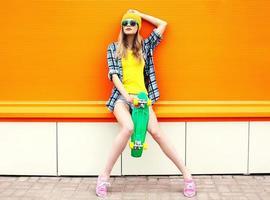 garota legal da moda hipster em óculos de sol e roupas coloridas. foto