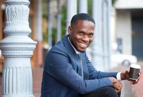 empresário sorridente sentado ao ar livre com uma xícara de café