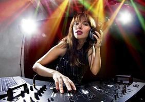 DJ feminina moderna tocando mp3s em uma festa foto