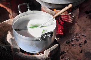 cozinhando leite de coco na panela, fervendo foto