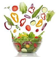 caindo vegetais frescos. salada saudável isolada foto