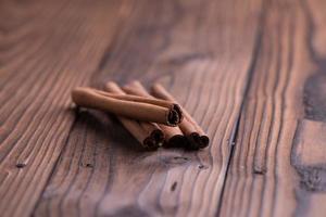 Paus de canela em fundo de madeira marrom foto
