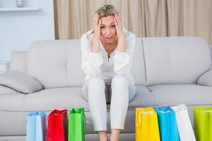 loira sentada no sofá com dor de cabeça perto de sacolas de compras foto
