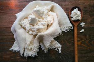 queijo cottage doméstico em um fundo de madeira foto