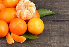 tangerinas com folhas na mesa cinza de madeira foto
